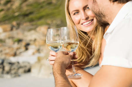 anniversary beach: Happy romantic couple enjoying glass of white wine on the beach. Cheerful couple toasting wineglasses for celebrating anniversary. Close up of couple toasting with white wine outdoor. Stock Photo
