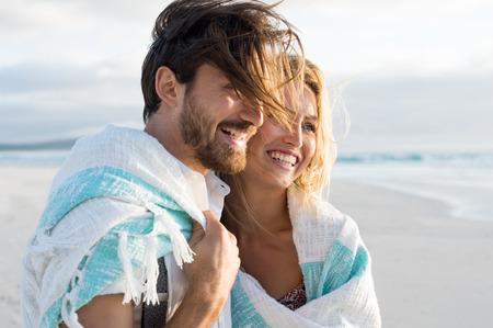 feliz pareja envuelta en manta en la playa. Pareja joven envuelta en una toalla en la playa. Sonriente pareja en la playa disfrutando de la vista del mar durante la puesta de sol. Foto de archivo