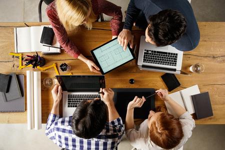 Hoge hoek weergave van team van architecten die lay-out op laptop ontwerpen. Architect die projecthuis toont aan zijn collega en samenwerken op laptop. Bovenaanzicht van zakenmensen in een vergadering. Stockfoto