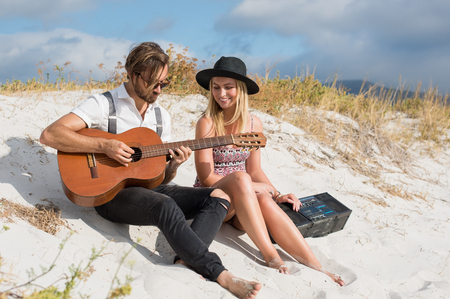 romantic love: Happy couple playing guitar on beach. Loving young couple sitting on beach. Smiling girl and guy with guitar and radio having fun on beach. Stock Photo