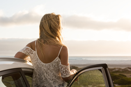 woman sunset: Young traveller woman enjoying sunset standing outside car. Serene woman leaning on car during sunset. Young woman on summer travel to the coast. Stock Photo