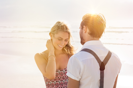 couples outdoors: Portrait of a young shy woman standing in front of a man. Young couple at beach in a conversation. Couple in love standing at sea shore at sunset. Stock Photo