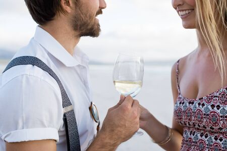 anniversary beach: Cheerful couple raising a toast at the beach. Young smiling couple celebrating anniversary at beach. Close up of couple holding glassess of white wine at beach.