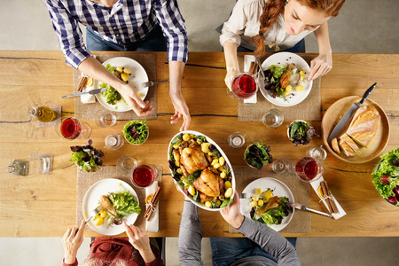 Draufsicht des Menschen Futternapf zu Freund vorbei. Erhöhte Ansicht der glücklichen jungen Freunde, die zusammen zu Hause zu essen. Glückliche Männer und Frauen Mittagessen mit gebratenem Huhn mit.