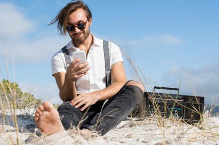 Knappe jonge man met behulp van smartphone zitten op het wilde strand. Hipster man in casual sitting en luisteren naar muziek met vintage radio outdoor. Man met behulp van mobiele telefoon op het strand.