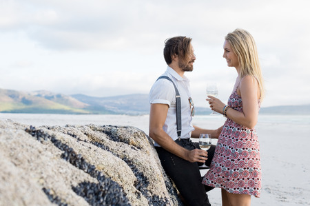 affectionate: Young couple in conversation while drinking a glass of white wine. Couple in love at beach looking at each other. Man leaning over rock in beach talking to girlfriend.