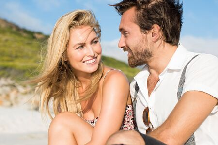 couples outdoors: Cheerful young couple sitting on the beach looking at each other. Couple in love at the beach. Smiling woman looking her boyfriend in a summer day. Stock Photo