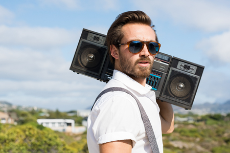 Radio: Portrait of a handsome young man holding radio near ears. Close up of hipster guy listening to music on a summer day. Man wearing sunglasses and holding on his shoulder a vintage radio. Stock Photo