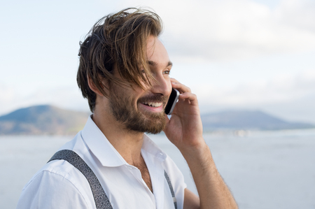 telephonic: Handsome man in a telephonic conversation at beach. Happy man talking on smartphone at beach. Cheerful guy receiving some good news through mobile phone.