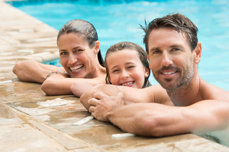Pretty little girl with her parents in swimming pool. Happy family smiling and looking at camera in swimming pool. Portrait of a happy couple with daughter in swimming pool. Stock Photo