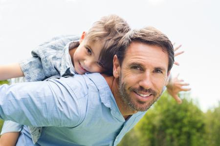 Gelukkig vader die op de rug rit geeft aan zijn zoon en kijken naar de camera. Gelukkig jong geitje rijden meeliften op zijn vader. Leuke jongen vliegen op vader.
