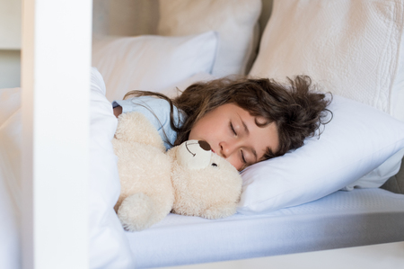 peacefully: Sweet child sleeping in bed. Little girl sleeping with teddy bear at morning. Cute little girl sleeping peacefully with teddy bear.