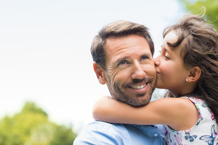 Portrait of a little girl kissing her dad on cheek. Pretty girl giving a kiss to her father outdoor. Loving child embrace and kissing her father. Stock Photo