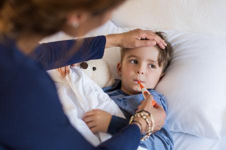 Zieke jongen met thermometer tot in bed en de moeder de hand nemen van de temperatuur. Moeder die temperatuur van haar zieke zoon die thermometer heeft in zijn mond. Ziek kind met koorts en ziekte tijdens de rust in bed.