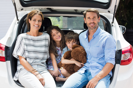 Family car trip on summer vacation. Happy smiling parents and two childreen in car having fun. Cute small boy holding teddy bear sitting with sister and parents in car for road trip with car.