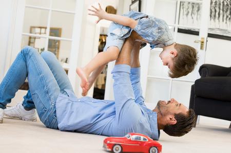 Het gelukkige vader spelen met zoon liggend op de vloer thuis. Jonge mens het spelen met kleine jongen. Vliegend kind genieten van het spelen met papa. Stockfoto