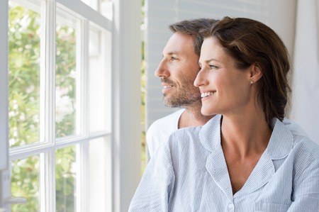 young happy couple: Cheerful young couple looking outside window. Portrait of smiling couple thinking about the future. Happy cheerful couple relaxing at home. Stock Photo