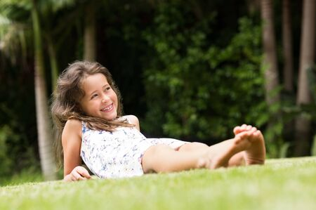 girl lying: Smiling little girl lying on green grass. Cute girl lying down and enjoying leisure and vacation. Happy smiling girl sitting barefoot on green grass in the park and thinking. Stock Photo