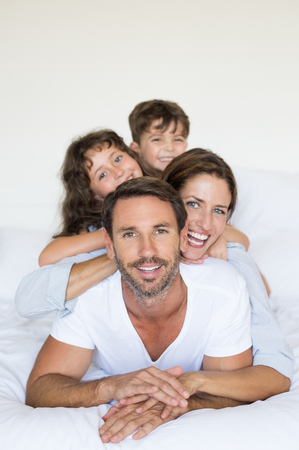 piramide humana: familia sonriente feliz acostado en la cama blanca. los padres jóvenes se extiende con el hijo y la hija en la cama teniendo diversión juntos. joven familia feliz que hace una pirámide humana y mirando a la cámara.