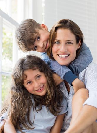 息子と娘の母親を抱きしめます。母は明るく晴れた朝に子供と楽しんでいます自宅に彼女の子供と幸せな笑顔ママの肖像は、カメラを見ています。 写真素材