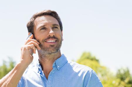 Gelukkige man praten over de telefoon op een fel zonnige dag en opzoeken. Glimlachende volwassen man met behulp van mobiele telefoon buiten. Portret van een man in een gesprek via de mobiele telefoon. Stockfoto