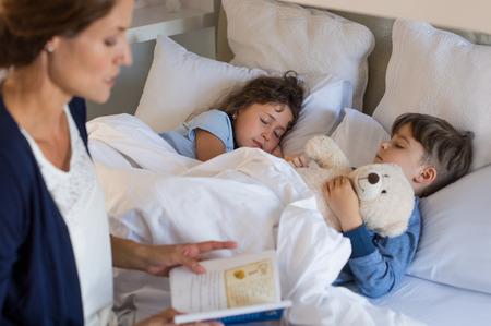 ベッドの時間物語を子供たちに読書の母。兄と妹に眠った。母息子と娘は、スリープ状態に置くこと。 写真素材