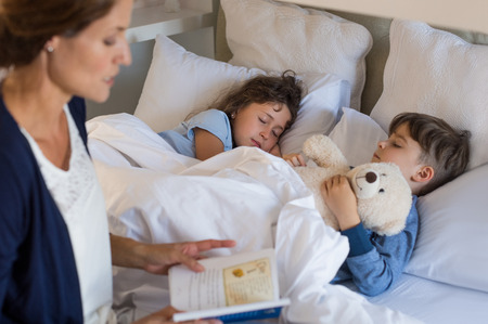 어머니는 아이들에게 침대 시간 이야기를 읽고. 형제와 자매는 평화롭게 자고. 어머니는 잠 아들과 딸을두고.