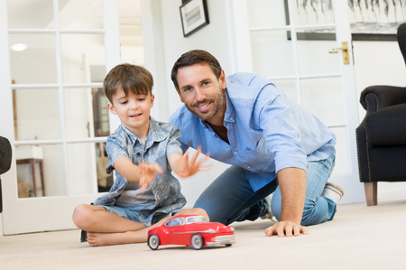 Father with little boy playing with toy car. Smiling father and happy son playing together in living room. Father spending quality time with son at home. Stock Photo