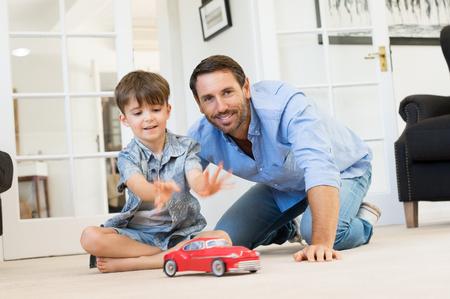 Otec se malý kluk hraje s autíčko. Úsměvem otec a syn hraje šťastní společně v obývacím pokoji. kvalitní čas výdaje otec se synem doma. Reklamní fotografie