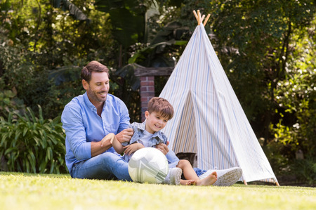 tickling: Cheerful father tickles his son at park. Happy child sitting outside a tent enjoying afternoon together with father. Father and son having fun with indian tent.