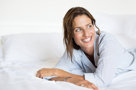 carefree: Cheerful woman lying on bed. Portrait of beautiful young woman thinking on bed in the morning. Happy smiling woman daydreaming on her future.
