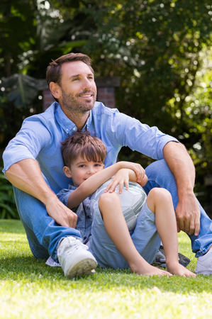 Young boy resting against father in a park holding soccer ball. Smiling father and son with a football in the park on a sunny day. Happy man and child sitting in the park with a soccer ball.