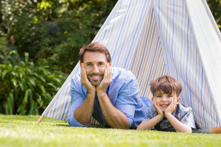 Father and son lying with their hands on cheeck. Young boy and his dad smiling and looking at camera. Portrait of happy family playing with tent in the garden.