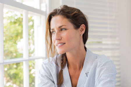 窓の近くに座って、外を見て、美しい熟女。明るく晴れた朝に窓の外を見て物思いにふける女。ナイトウェア思考の女性。
