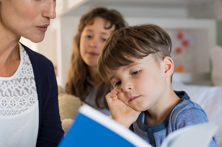 tells: Mother reading bedtime stories with her childreen. Little boy is falling asleep while mom tells him the story. Mother helping young boy read books at night. Stock Photo