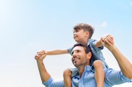 Vader geeft zoon rijden op terug in park. Portret van gelukkige vader die zoon piggyback ritje op zijn schouders en opzoeken. Leuke jongen met moeder spelen buiten. Stockfoto - 56370622