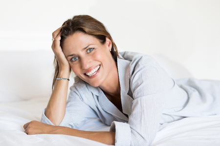 Cheerful woman lying on bed and looking at camera. Beautiful smiling woman lying on front on her bed at home. Portrait of happy woman in pajamas at home.