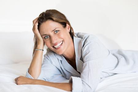Vrolijke vrouw die op bed ligt en camera bekijkt. Mooie glimlachende vrouw die op voorzijde op haar bed thuis ligt. Portret van gelukkige vrouw in pyjama's thuis. Stockfoto