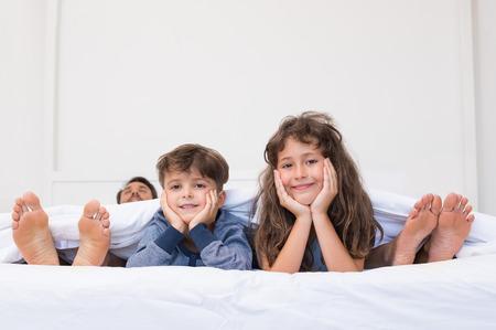 Porträt von fröhlichen glücklichen Kinder liegen auf dem Bett vor die Füße der Eltern. Sohn und Tochter liegend Blick in die Kamera. Junge Kinder in schelmischen Stimmung.
