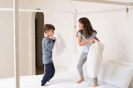 brother sister fight: Siblings fighting using pillow in bedroom. Happy laughing brother and sister having a pillow fight in bedroom. Kids playing with pillows on parent bed. Stock Photo