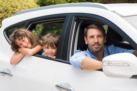 Kinderen zitten in de auto uitkijken ramen. Schattige kinderen in de auto te gaan kamperen met vader. Klein jong gezin reist met huurauto en kijken naar de camera.