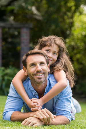 piramide humana: Joven padre e hija acostada en la hierba verde. hija feliz se sienta en padre hacia atrás y sonriendo. Niña joven que hace una pirámide humana con su padre y mirando hacia arriba. Foto de archivo