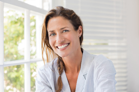 Portrait der schönen reifen Frau sitzt und lächelnd. Frau Gefühl frisch auf einem hellen, sonnigen Morgen zu Hause. Frau sitzt in Nachtzeug in der Nähe der Fenster und Blick in die Kamera. Standard-Bild