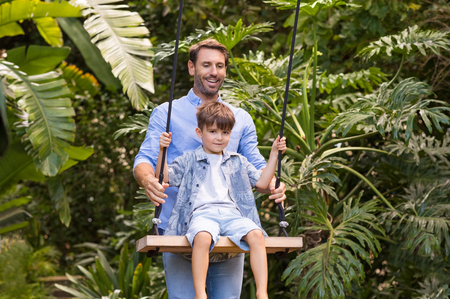 niños sentados: hijo feliz que se divierte en un columpio con su padre. Padre alegre que ayuda al hijo swing. padre empujando a su hijo en la sonrisa del oscilación. Foto de archivo