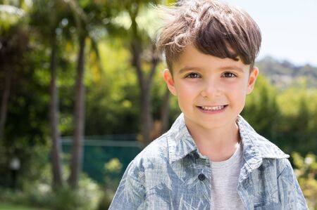 boy kid: Portrait of a little happy boy looking at camera. Happy kid smiling with toothy smile. Beautiful child in casual outdoor. Stock Photo