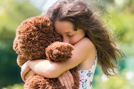 Emocionální dívka objala medvídka. Mladá roztomilá holčička objímal hnědý kožich medvídka. Holčička v lásce s její věci hračku.