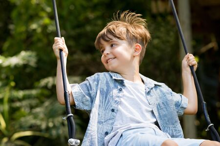 children at play: Young boy having fun swinging. Smiling child playing on a swing at park. Portrait of happy little boy swinging on swing on a bright sunny day.