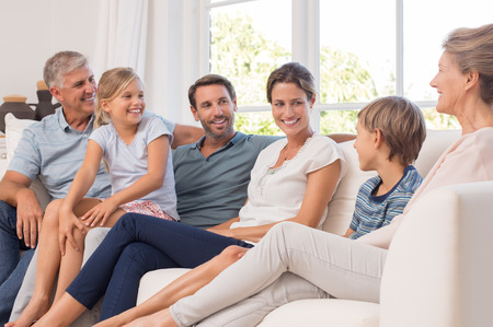 Happy generation family sitting on couch at home and talking. Portrait of extended family group sitting together in a conversation. Smiling mother and father with children and grandparent.