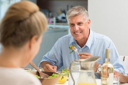Portrét starší muž jíst jídlo při pohledu na manželku. Zdravý starší muž s obědem doma. Veselý pár si oběd. Reklamní fotografie