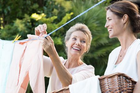 helping: madre de más edad y su pequeña hija al aire libre para secar la ropa colgando. hija sonriente ayudar a la madre con lavadero. madre e hija alegres en la conversación mientras que cuelga la ropa exterior.